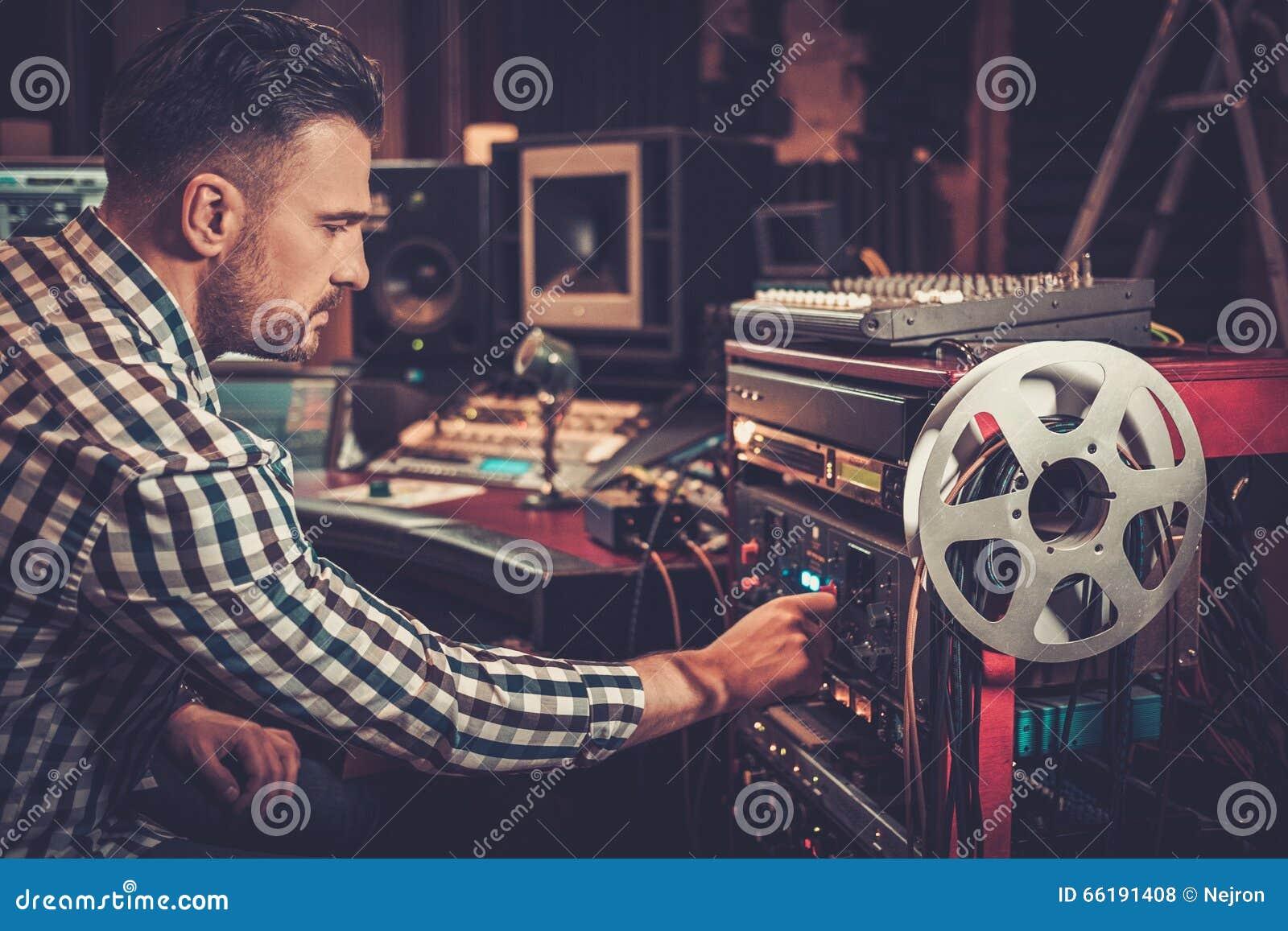 Solid tekniker som arbetar med yrkesmässig ljudutrustning i inspelningstudion