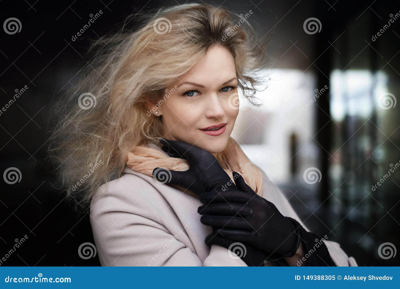 Solig modestil f?r sommar St?ende av en ung stilfull kvinna utomhus, den ikl?dda moderiktiga dr?kten och svarta handskar