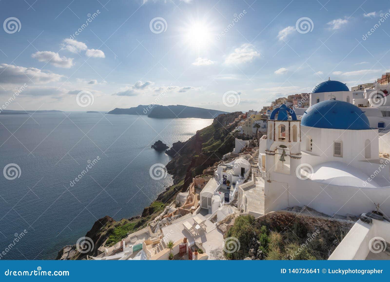 Solnedgång över blåa kupolformiga kyrkor på calderaen på Oia på den grekiska ön av Santorini