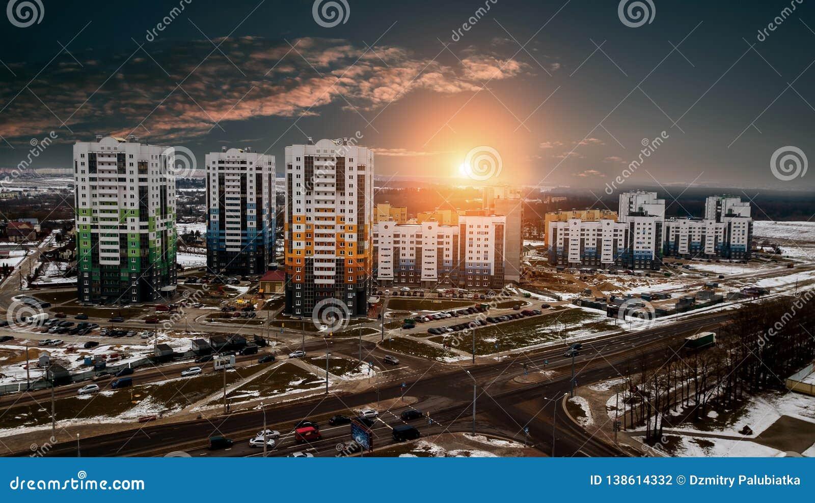 Solnedgång över ett bostadsområde med mång--våning byggnader