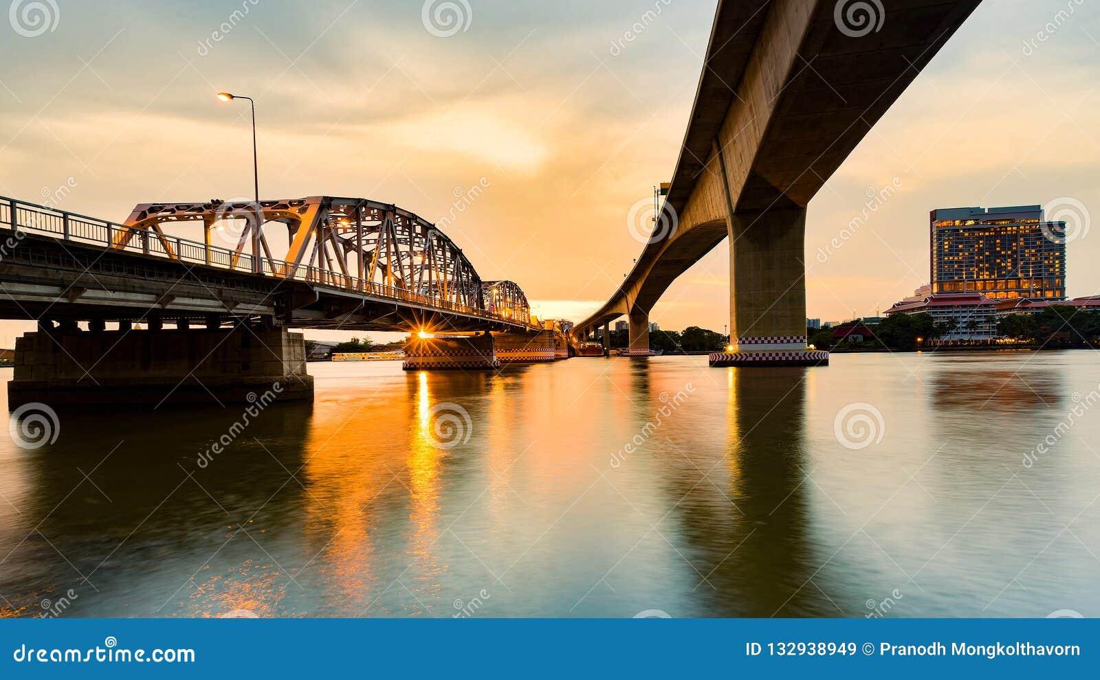 Solnedgång över floden under bron