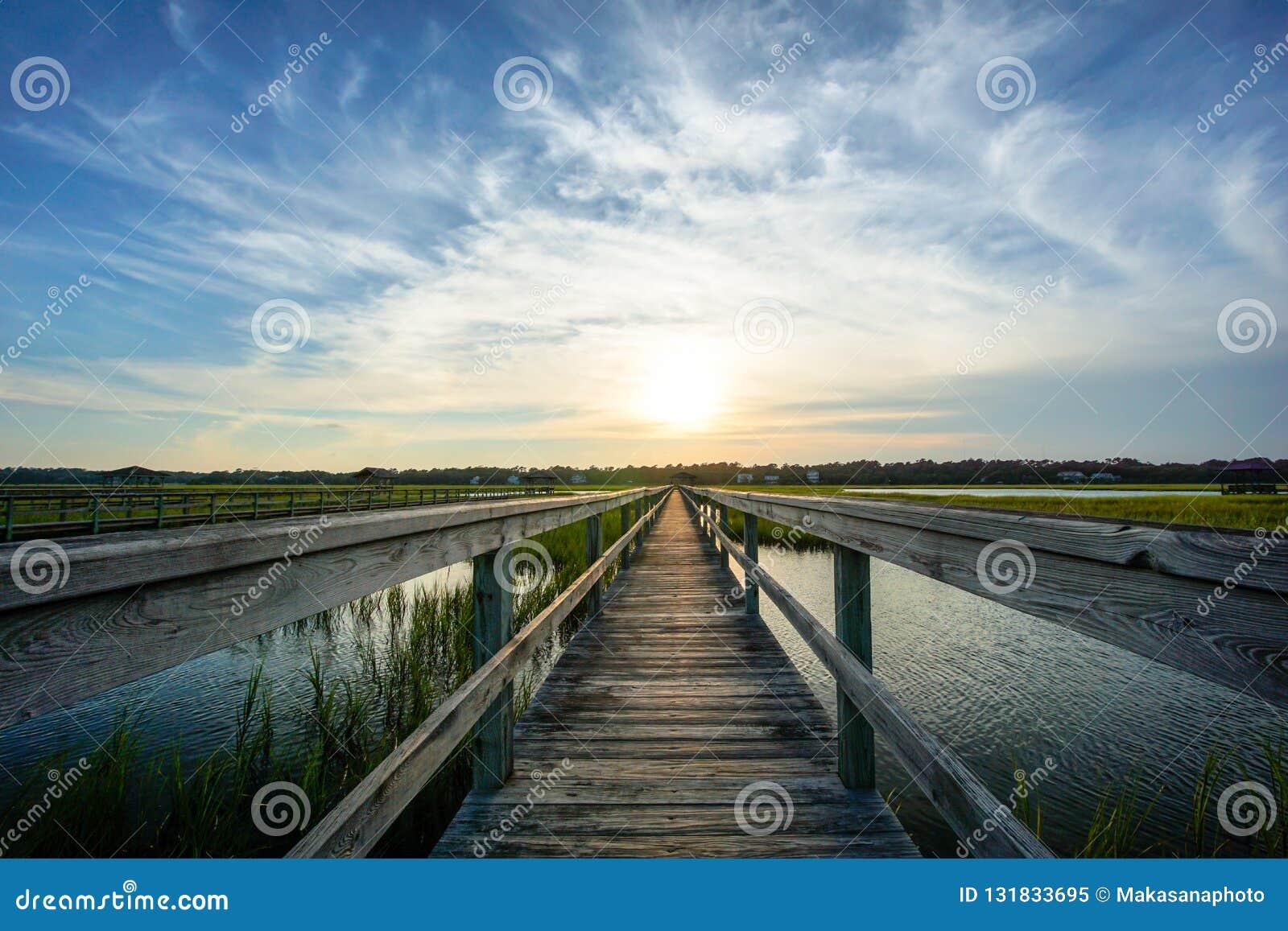 Solnedgång över kust- vatten med en mycket lång trästrandpromenad
