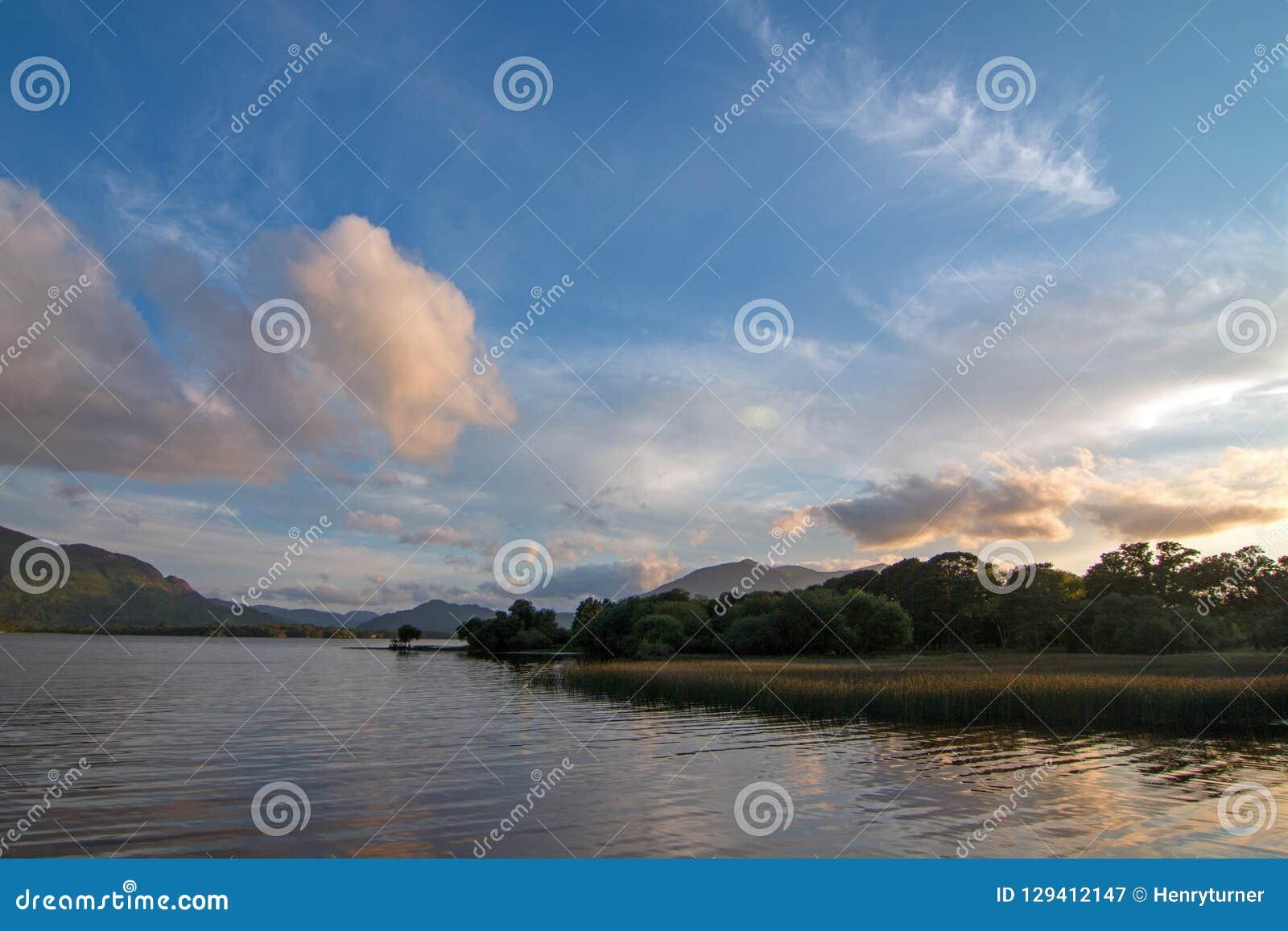 Solnedgång över loughen Leane [sjön Leane] med vattenlillies på cirkeln av Kerry i Killarney Irland