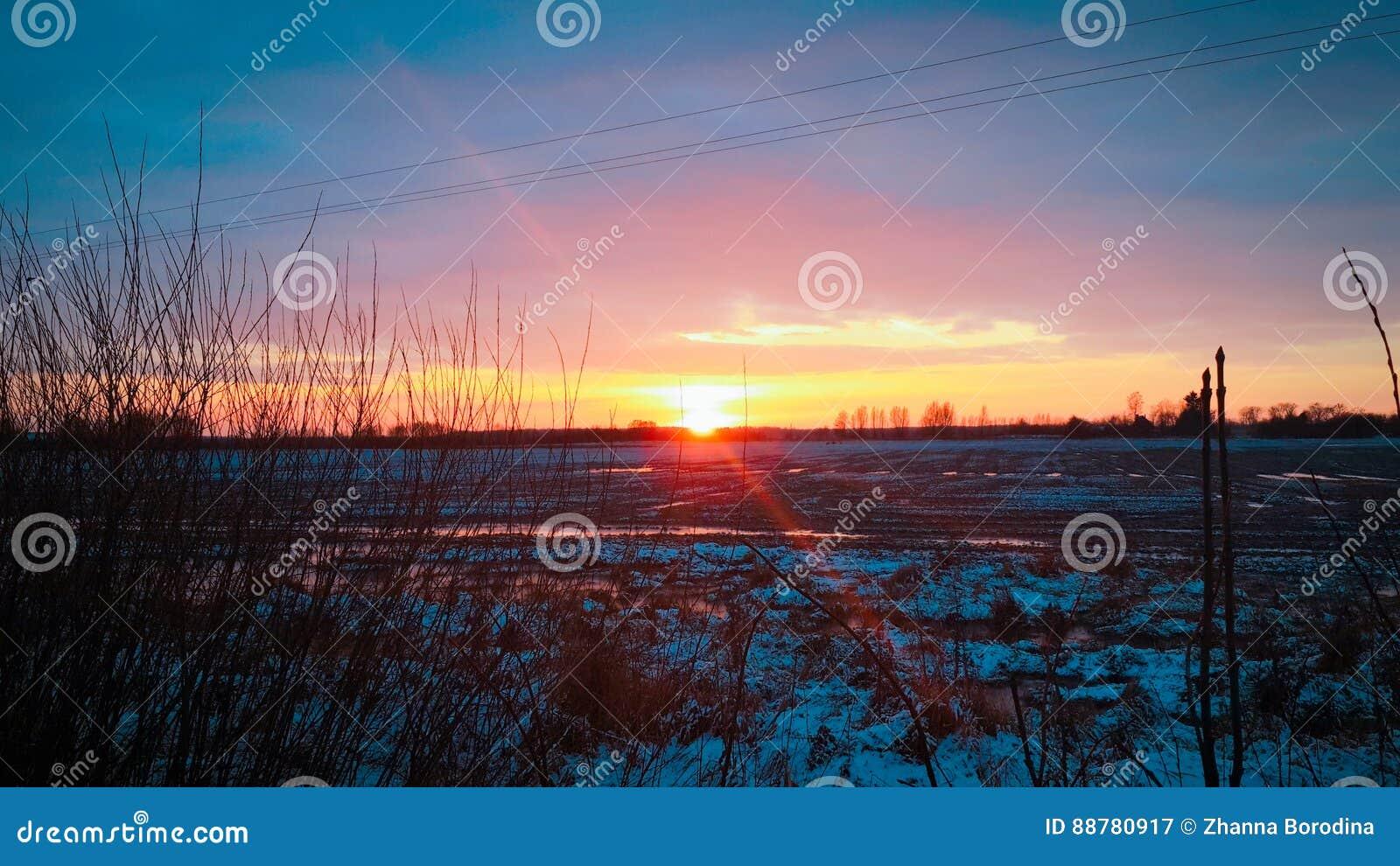 Solnedgång över snö-täckt fält