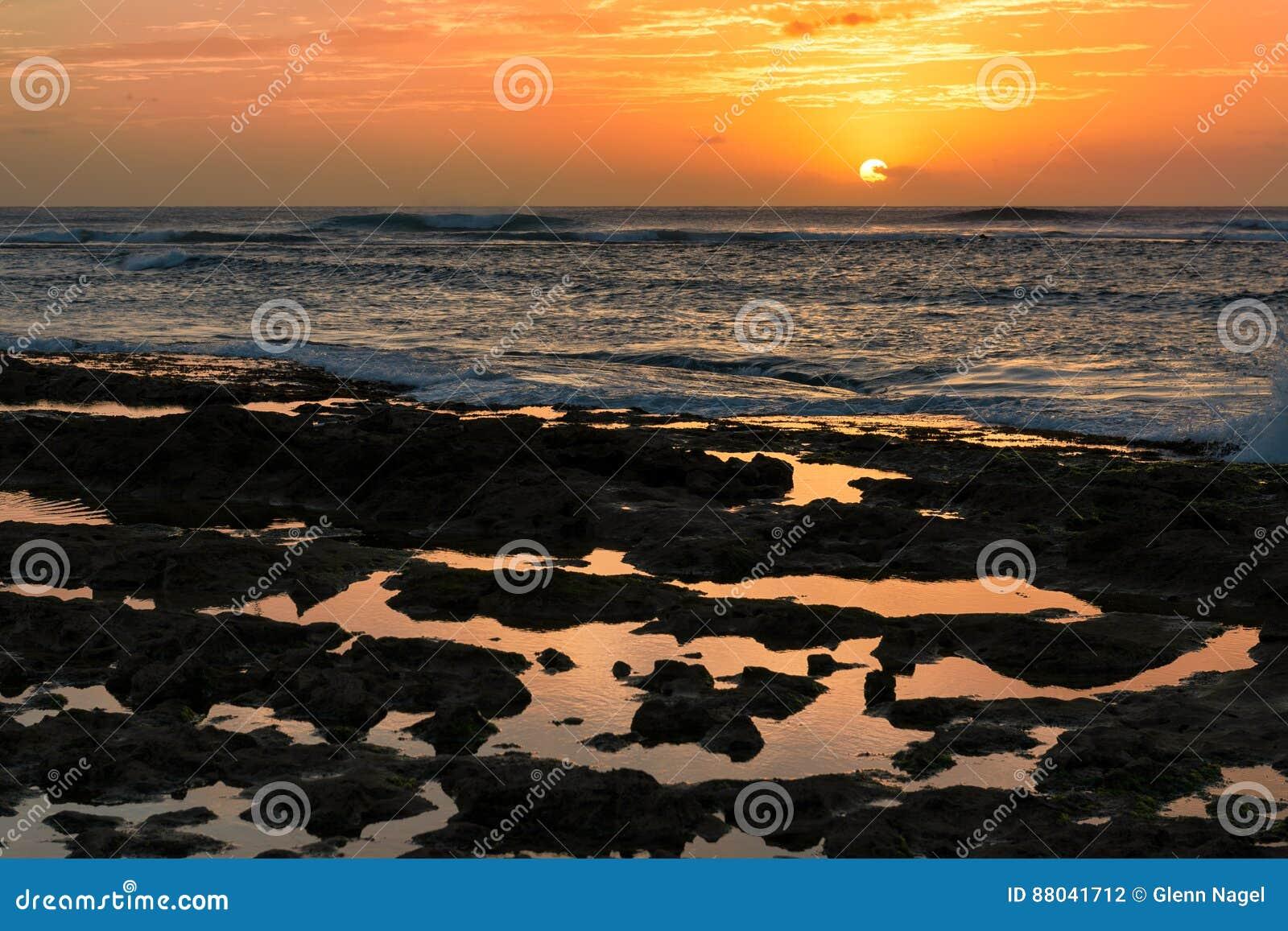 Solnedgång av stenig tidvattentips i Waianae, Hawaii