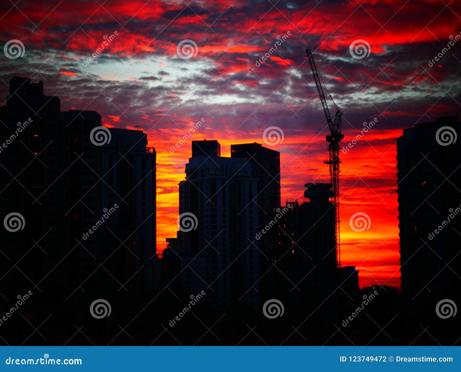 Solnedgång bak byggnader med härlig molnig himmel