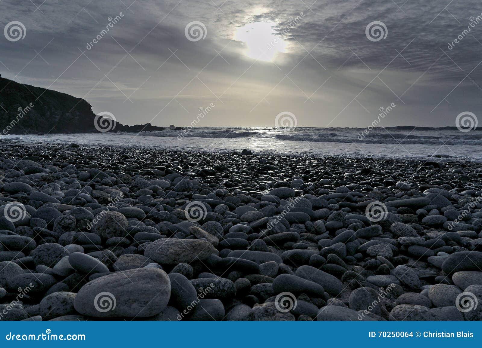 Solnedgång för strandpebbleseascape