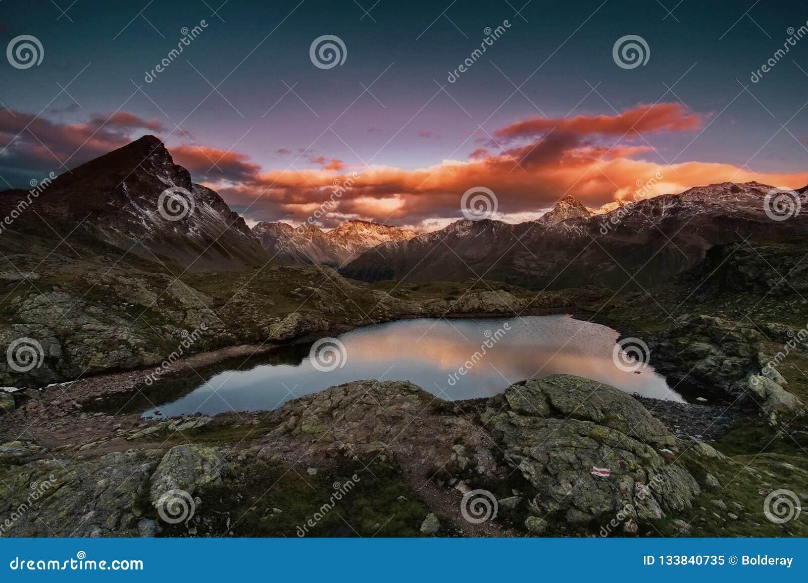 Solnedgång i bergen Den lilla sjön, även i vinter, vattentemperaturen är + 30 grader Dalen av Geysers