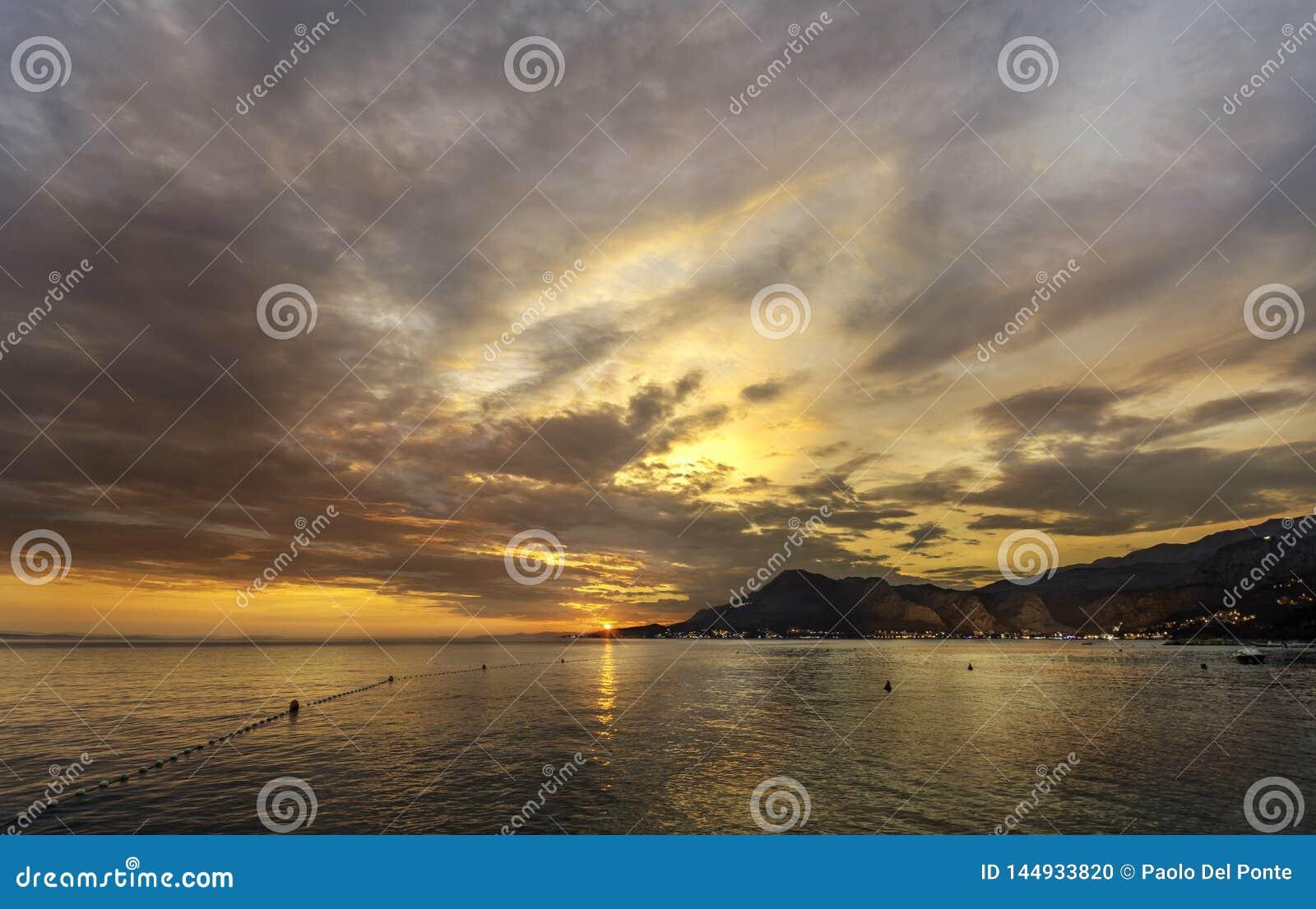 Solnedgång i Omis Dalmatia med dramatiska moln på himmel- och nattljus i stad på kusten på rätsidan och det öppna havet på