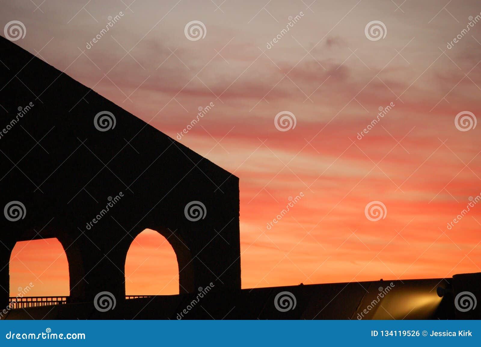 Solnedgång med konturn av strukturen med bågar