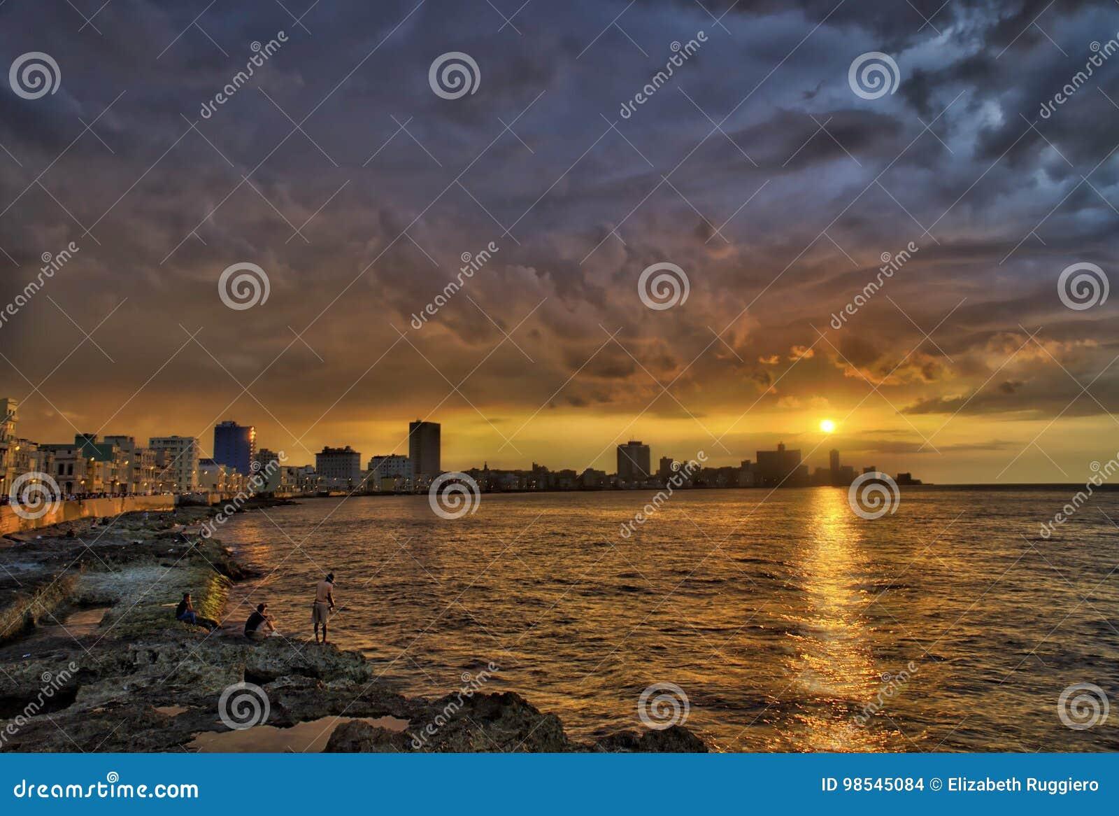 Solnedgång och dramatiska moln över havannacigarrhorisont med fiskare i förgrund