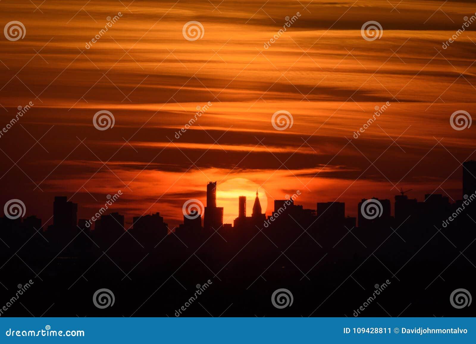 Solnedgång och staden