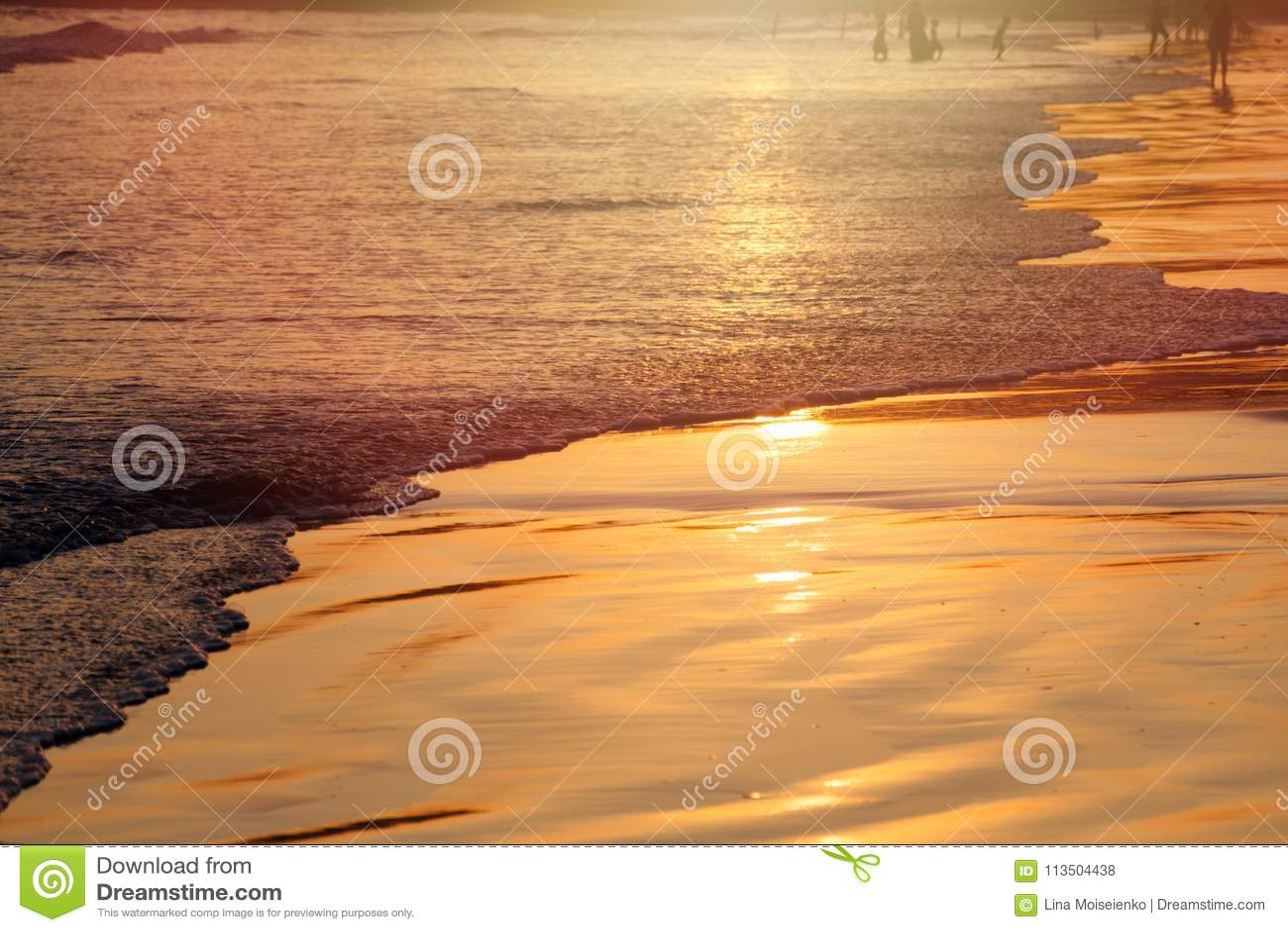 Solnedgång på den tropiska stranden i Sri Lanka - guld- färg vinkar havsvatten, kontur av folk på bakgrund