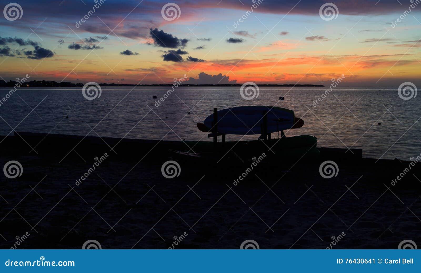 Solnedgång på fjärden med kanoter och kajaker som konturer i sommar