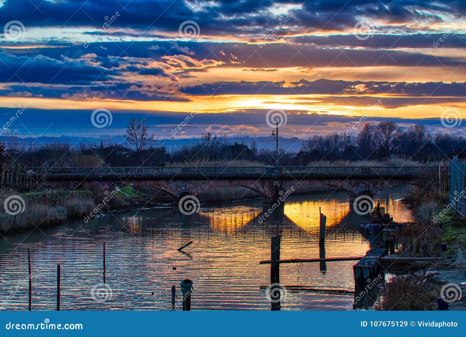 Solnedgång på floden under den forntida järnvägsbron