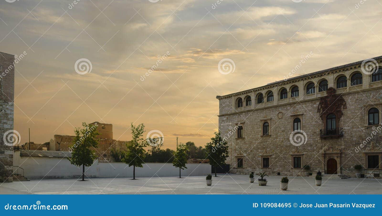 Solnedgång som ses från borggården av slotten för ärkebiskop` s i Alcala de Henares, Spanien, sikt av den huvudsakliga fasaden