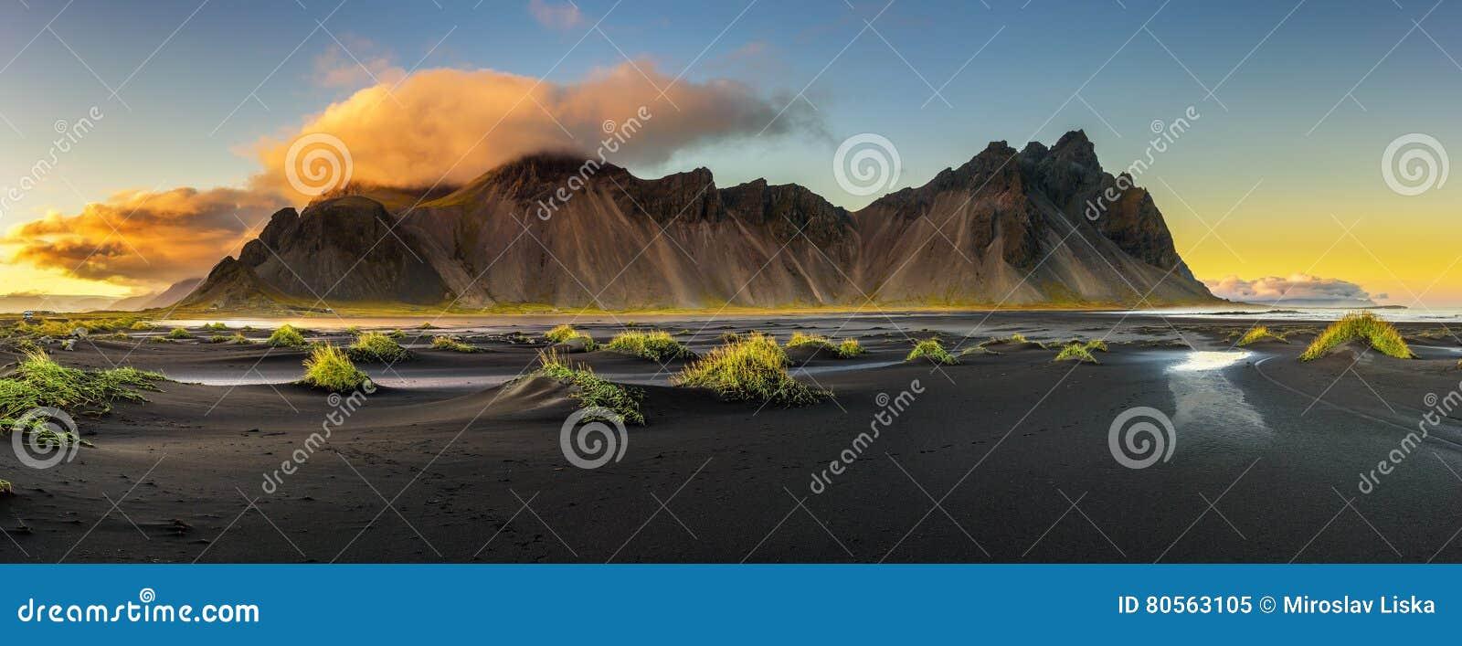Solnedgången ovanför Vestrahorn och dess svarta sand sätter på land i Island