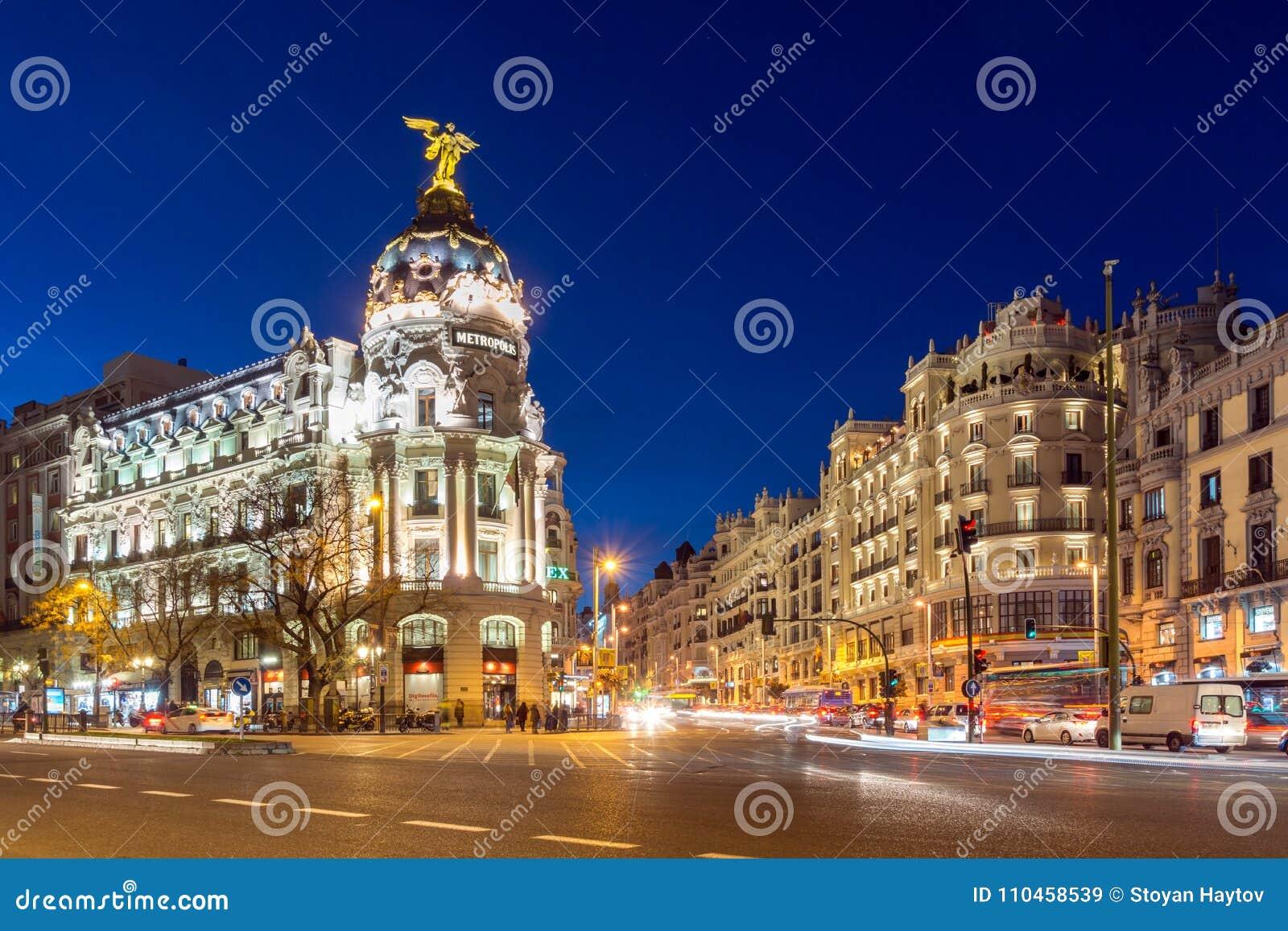 Solnedgångsikt av Gran via och metropolisbyggnad i stad av Madrid, Spanien