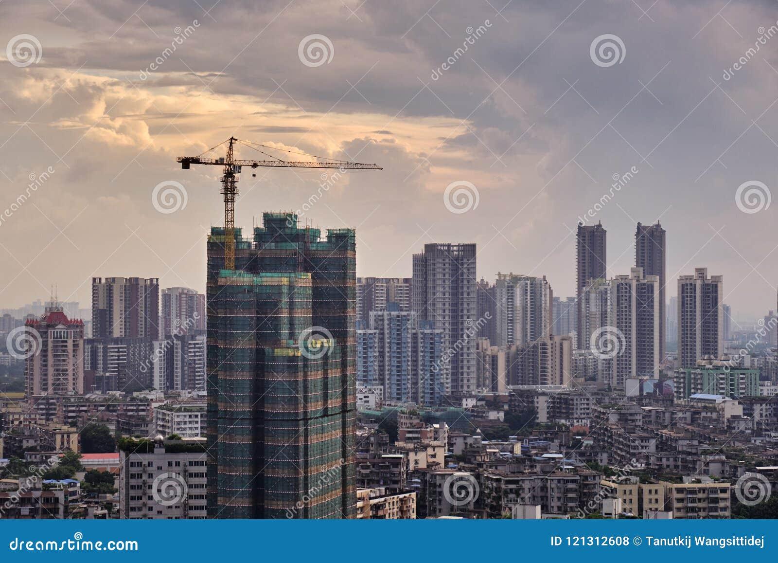 Solnedgångsikt av under-konstruktionsbyggnad och många hög-slut företag liksom finans, försäkring, fastighet, Guangzhou stad,