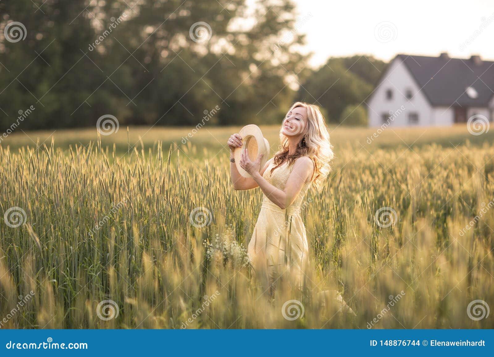 Solnedg?ng i sommar lantlig livstid En ung kvinna i f?ltet kastar en hatt Lantlig stil