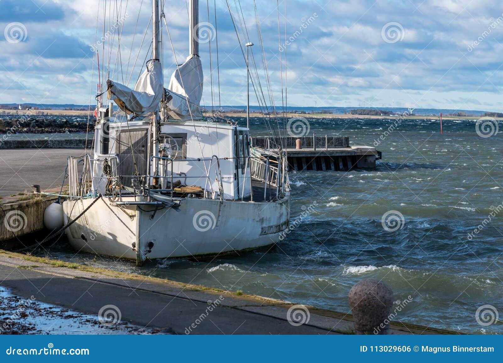 Solo barco de navegación blanco, amarrado en el puerto