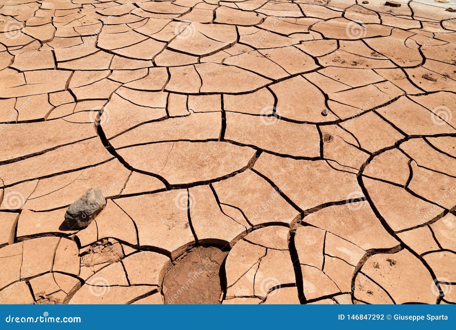 Solo de argila rachado na frente das montanhas flamejantes província em China, Xinjiang Localizado na depressão de Turpan