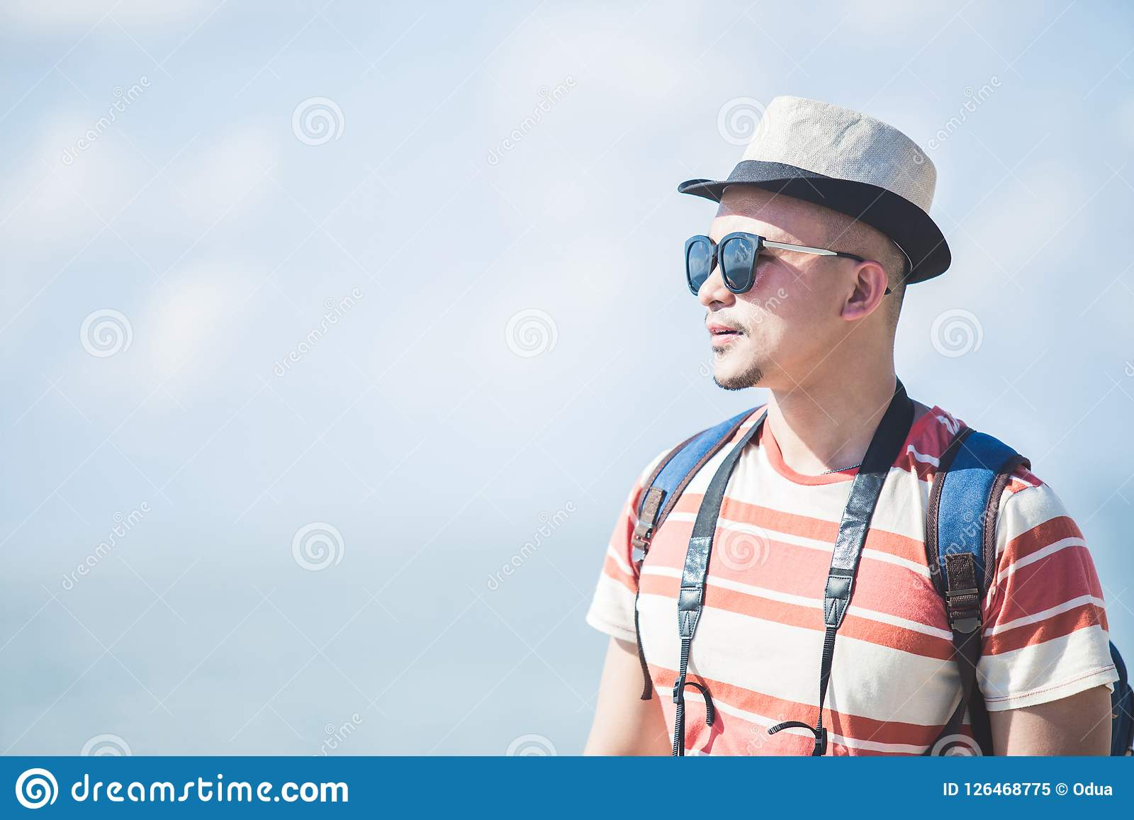 Solo traveller wearing summer hat and sunglasses during vacation