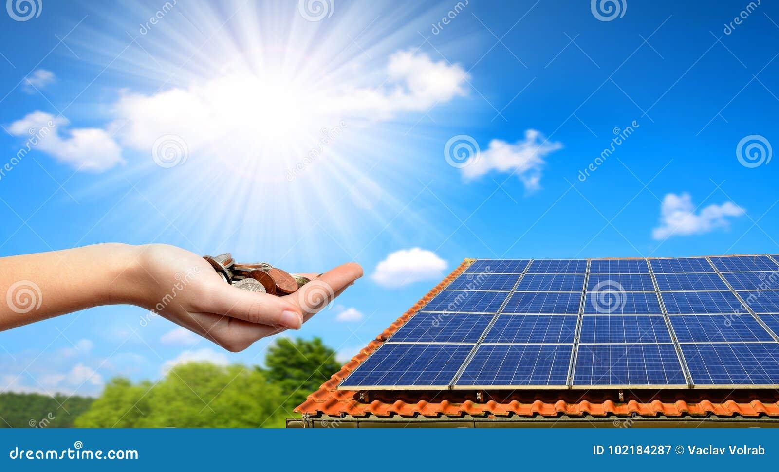 Solpanel på taket av huset och mynten i hand