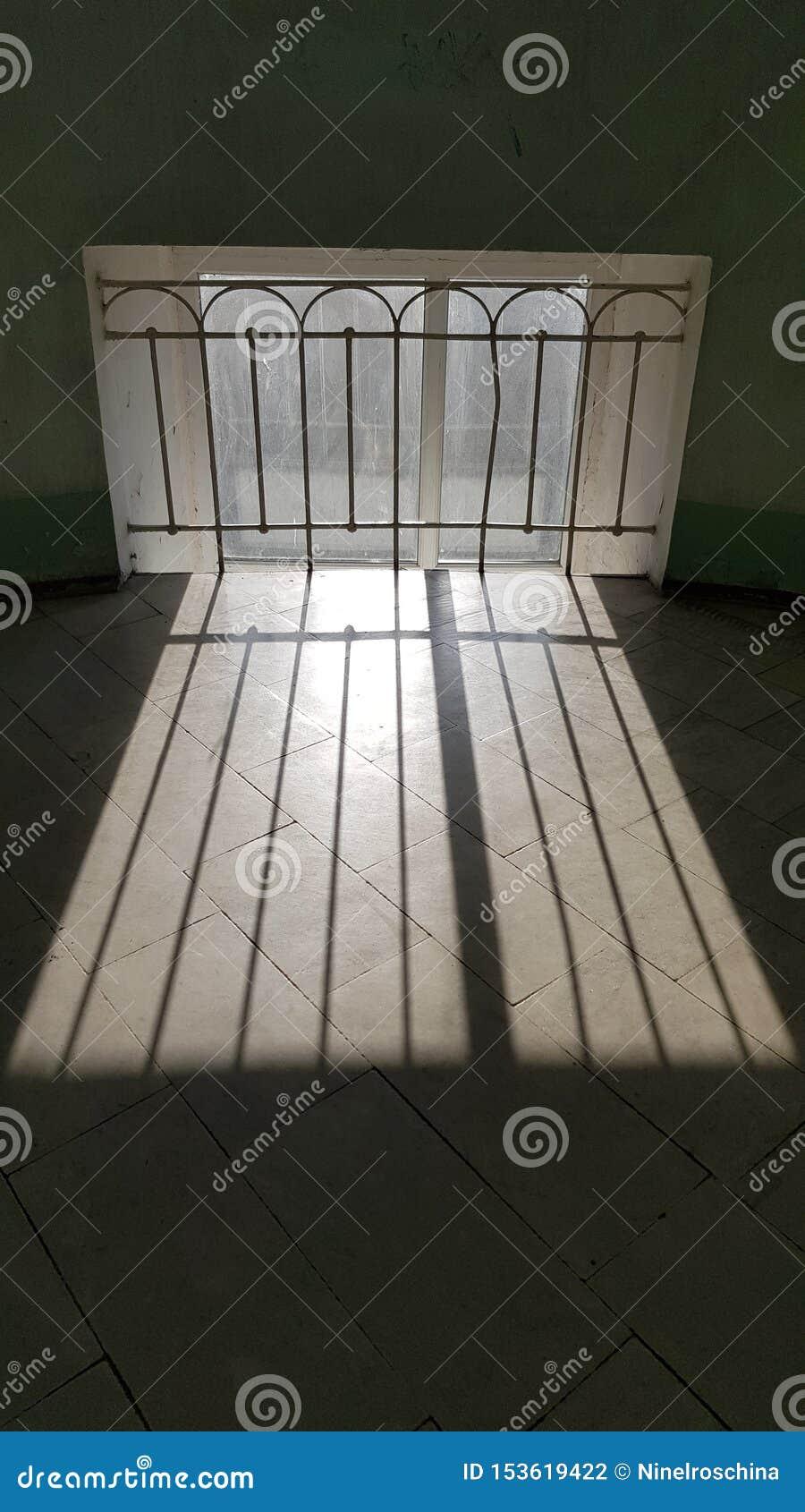 Solstråleband på belagt med tegel golv för sten nära det retro stilfönstergallret