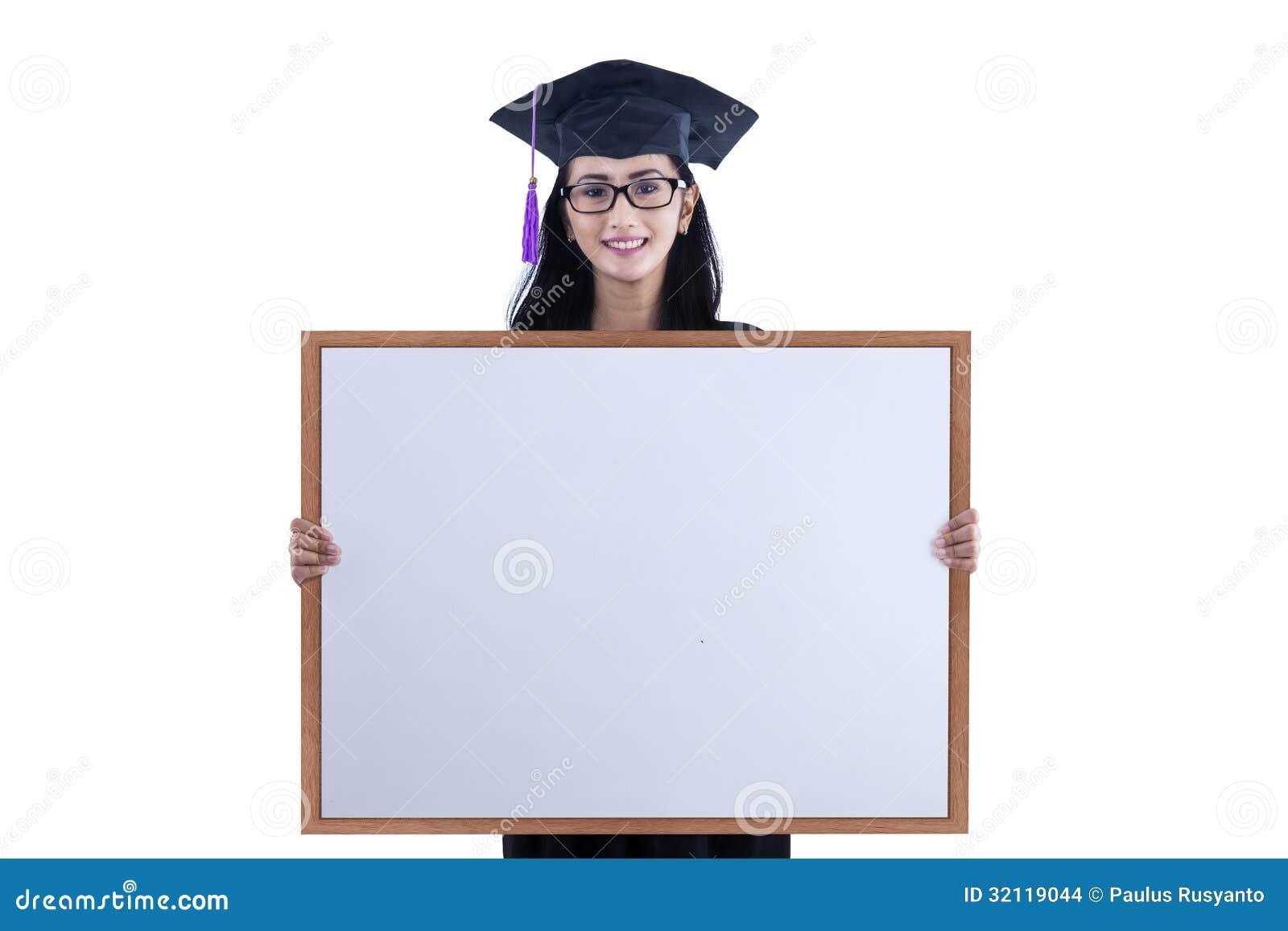 3dfa9b872 Muchacha feliz del estudiante de la graduación con la cartelera en blanco