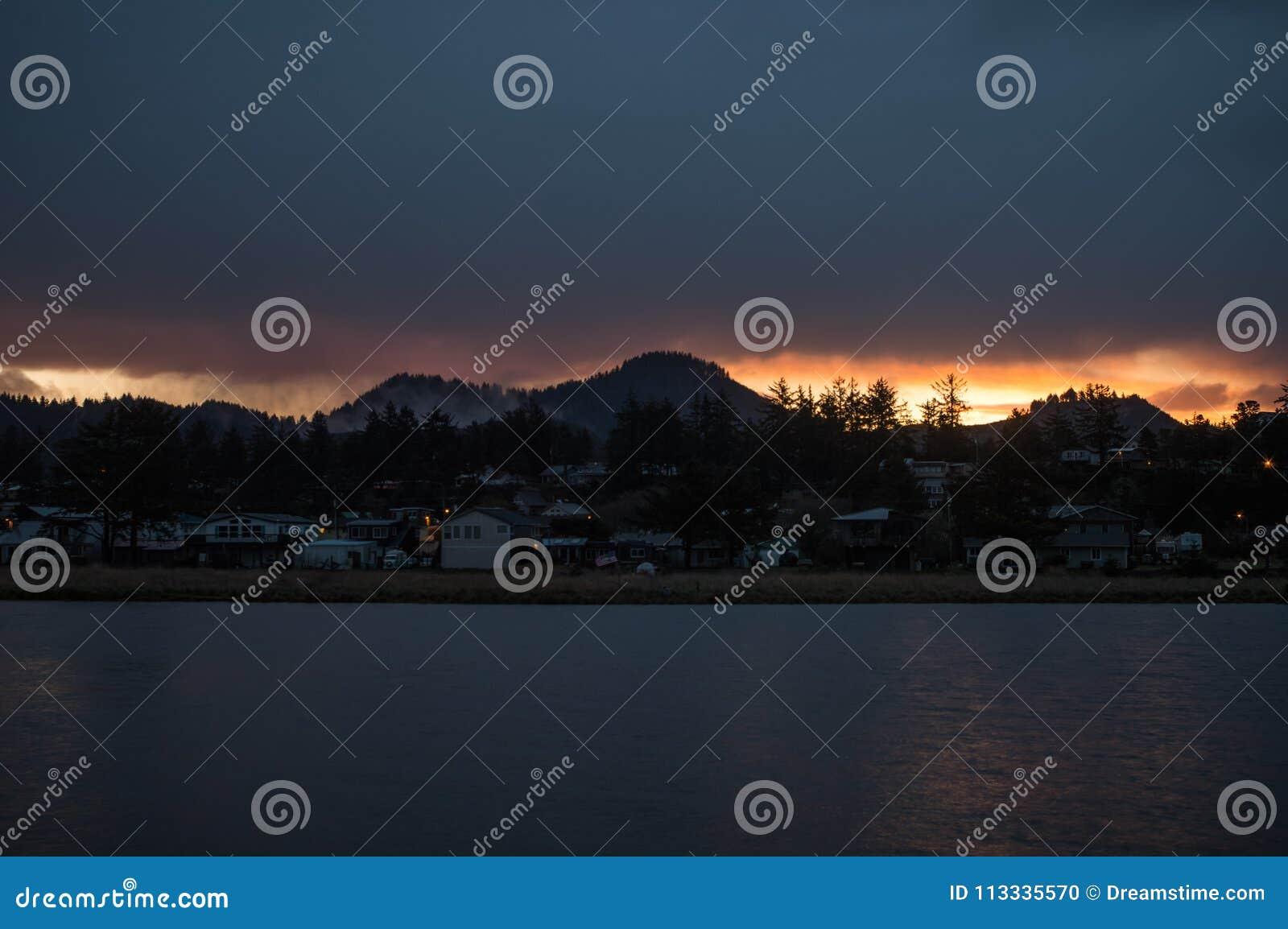 Soluppgång bak kullen framme av floden på den kust- Oregon staden