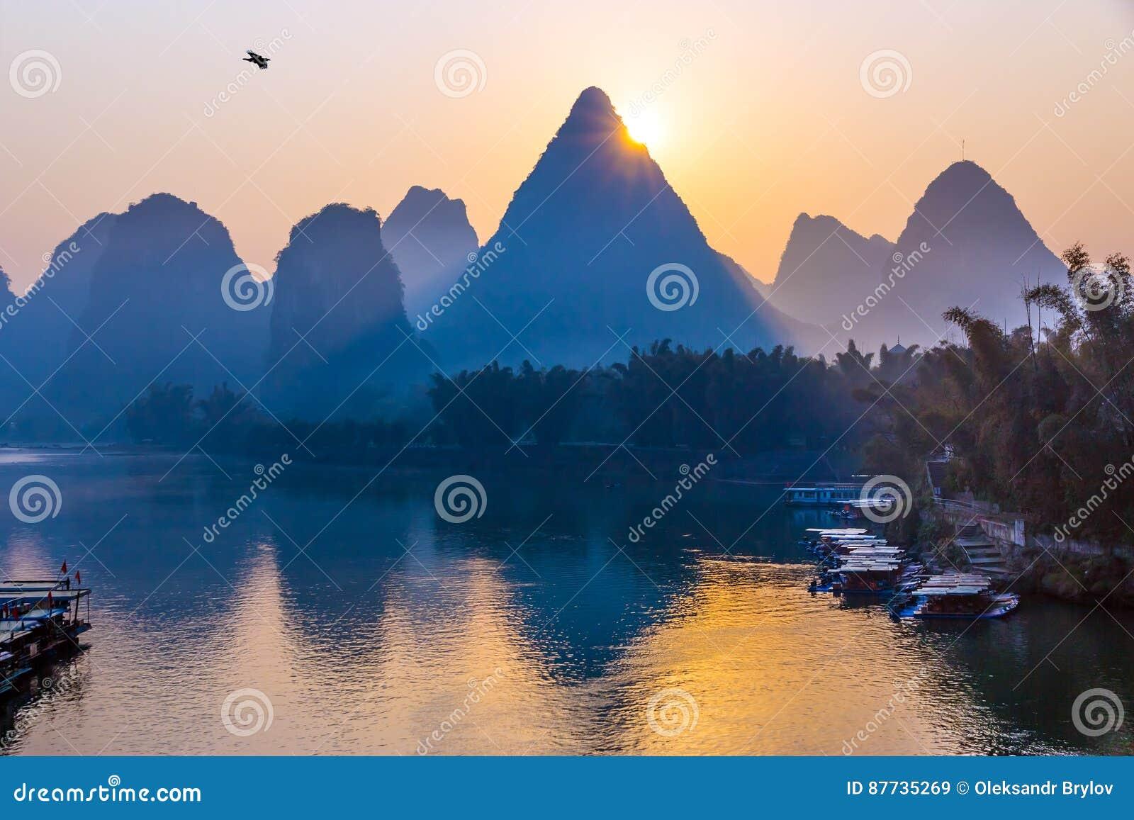 Soluppgånglandskap för traditionell kines med vatten och berg