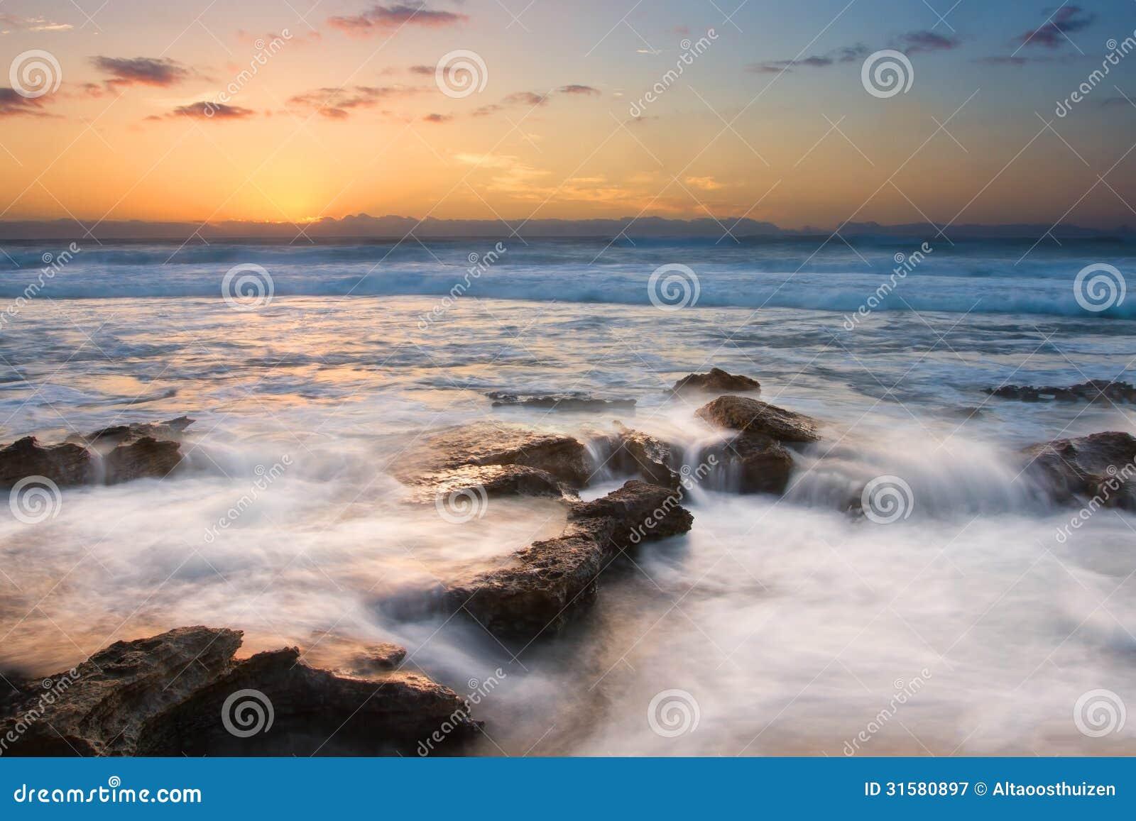 Soluppgånglandskapet av havet med vågmoln och vaggar