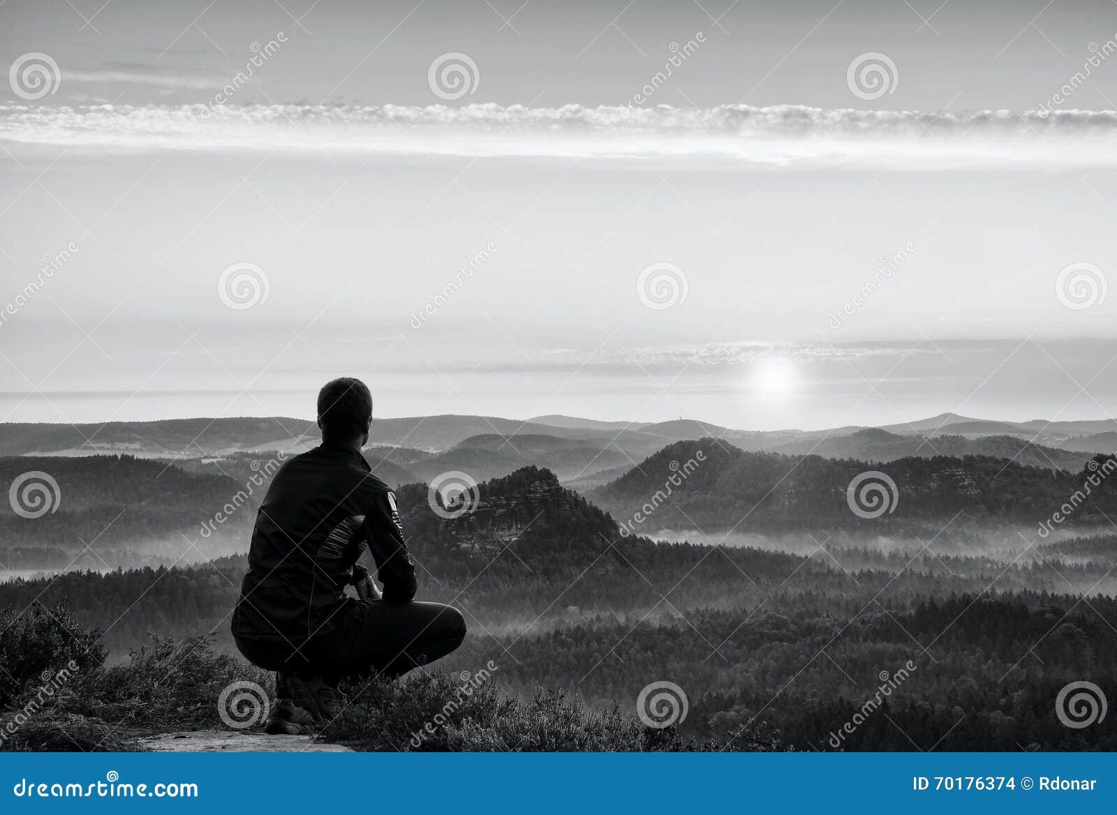 Soluppgångsportar Fotvandraren in i mörk sportwear i squattingposition på en vagga i ljungbuskar, tycker om landskapet