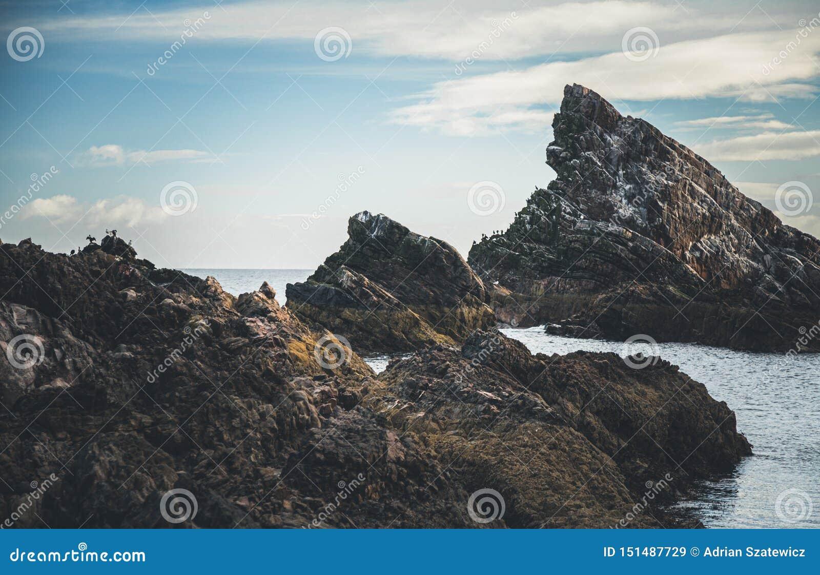 Soluppgångtid vid pilbågen Fiddle Rock i Skottland