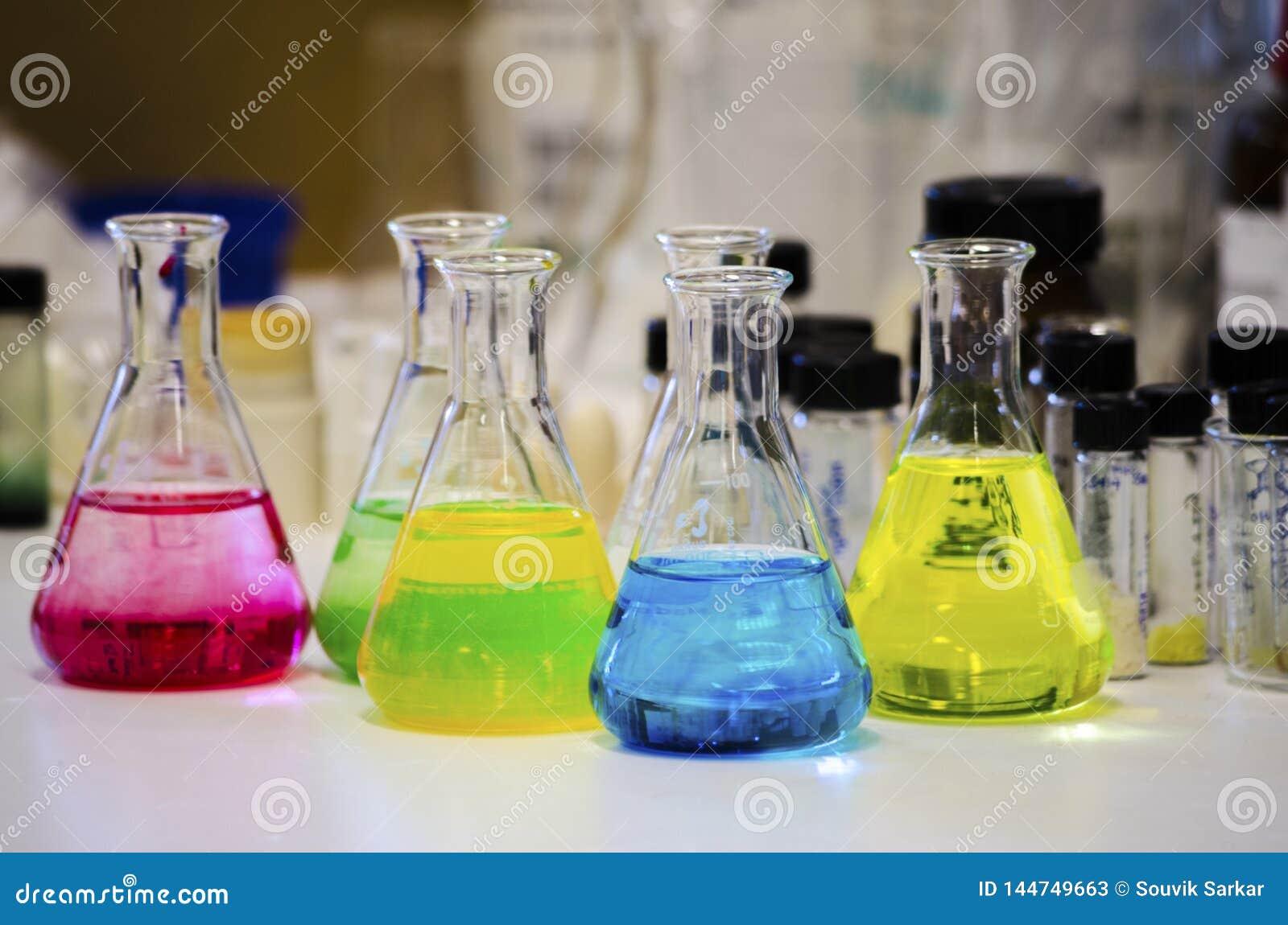 Solution colorée différente dans la fiole conique sur un banc dans un laboratoire de chimie avec l expérience de chimie organi