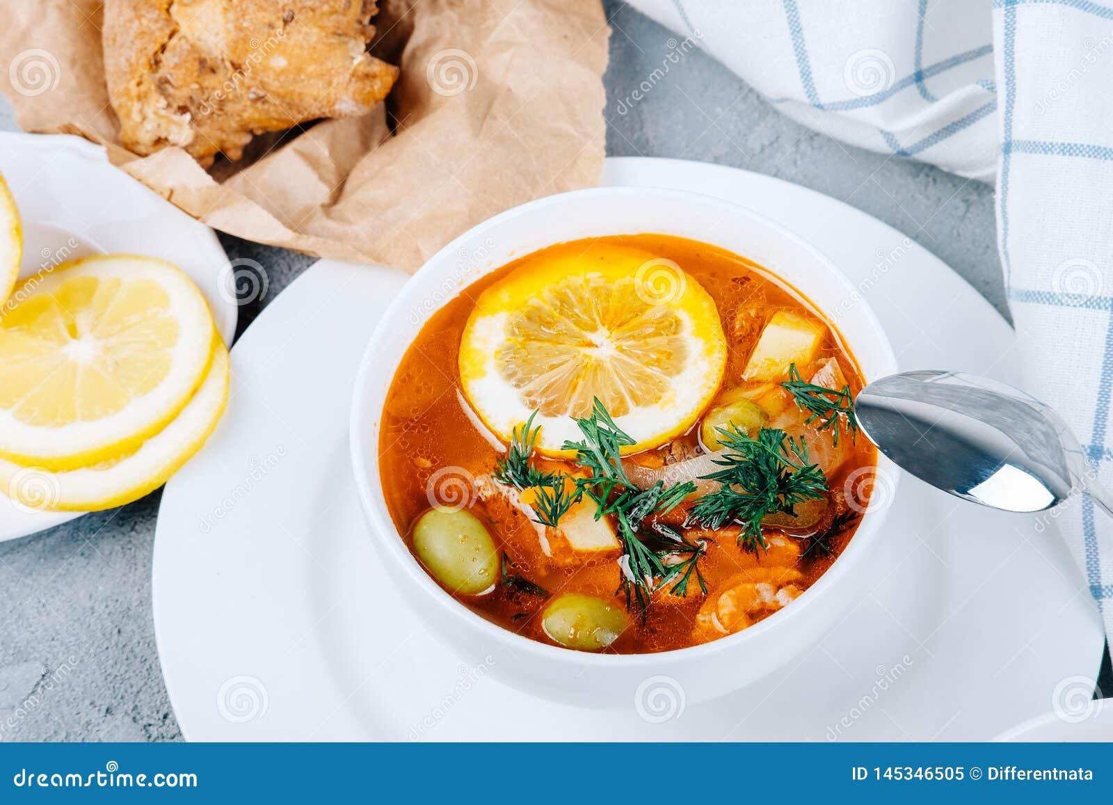 Solyanka en tjock soppa av grönsaker och kött som tjänas som med citronen och oliv
