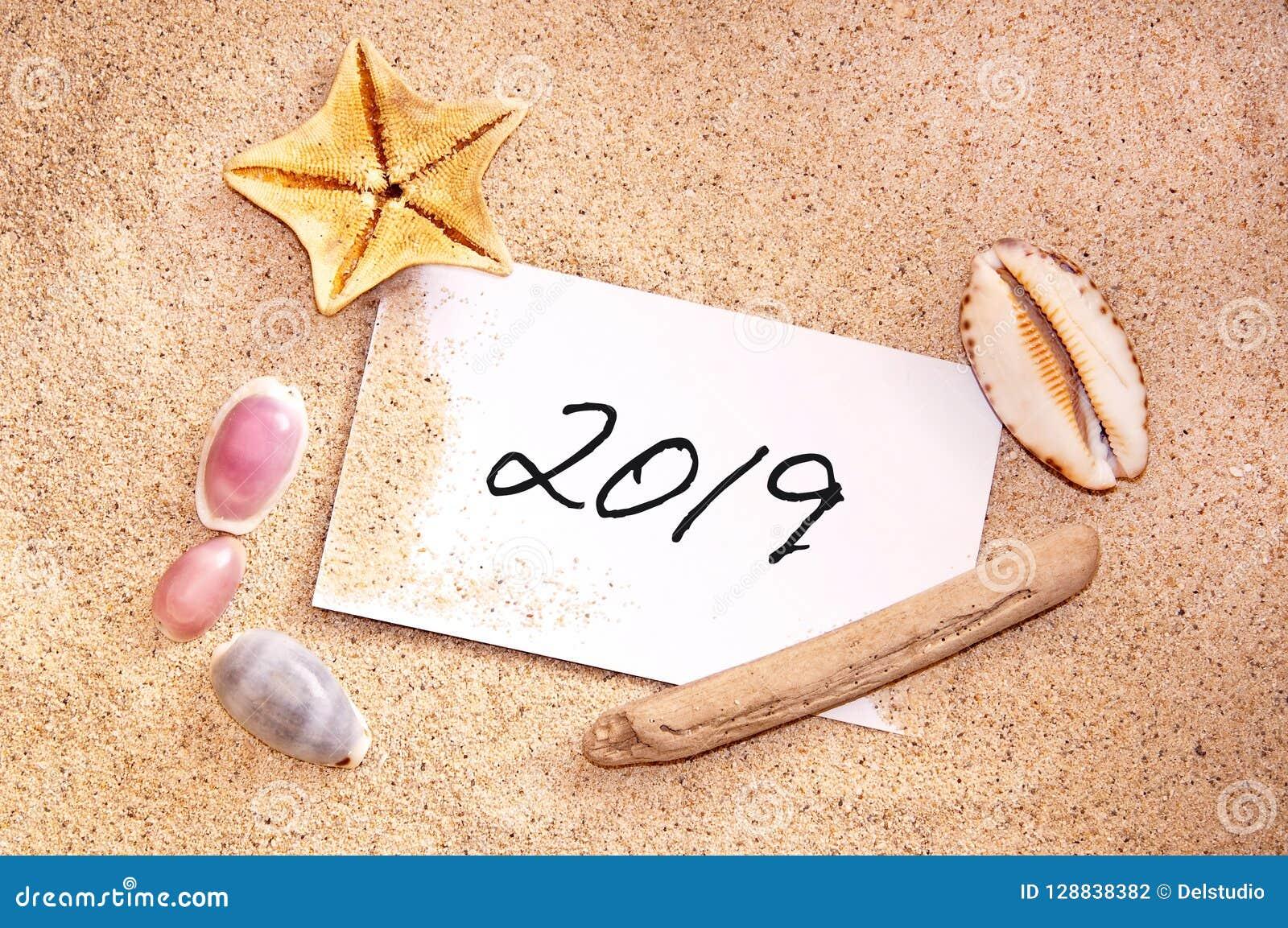 2019 som är skriftlig på en anmärkning i sanden med snäckskal
