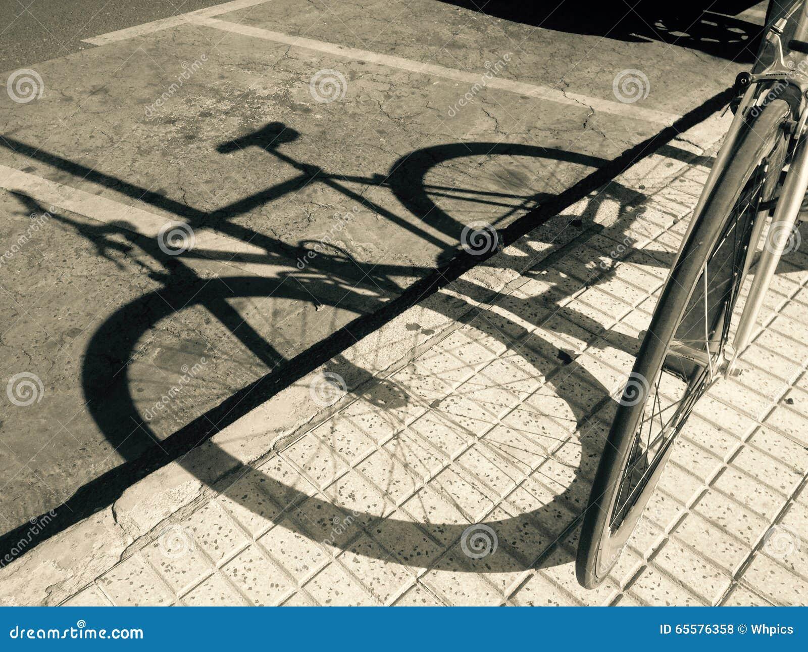 Sombra da bicicleta estacionada sobre a estrada asfaltada