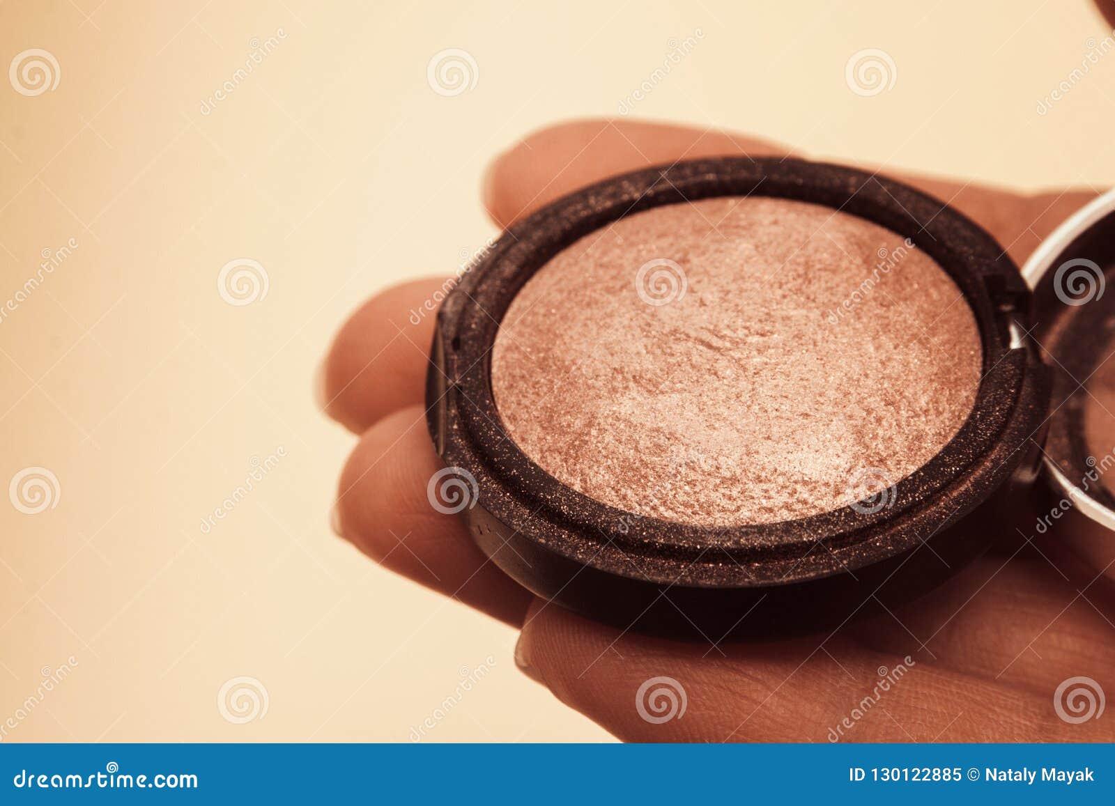 Sombra de ojos marrón de oro quebradiza abierta en la mano