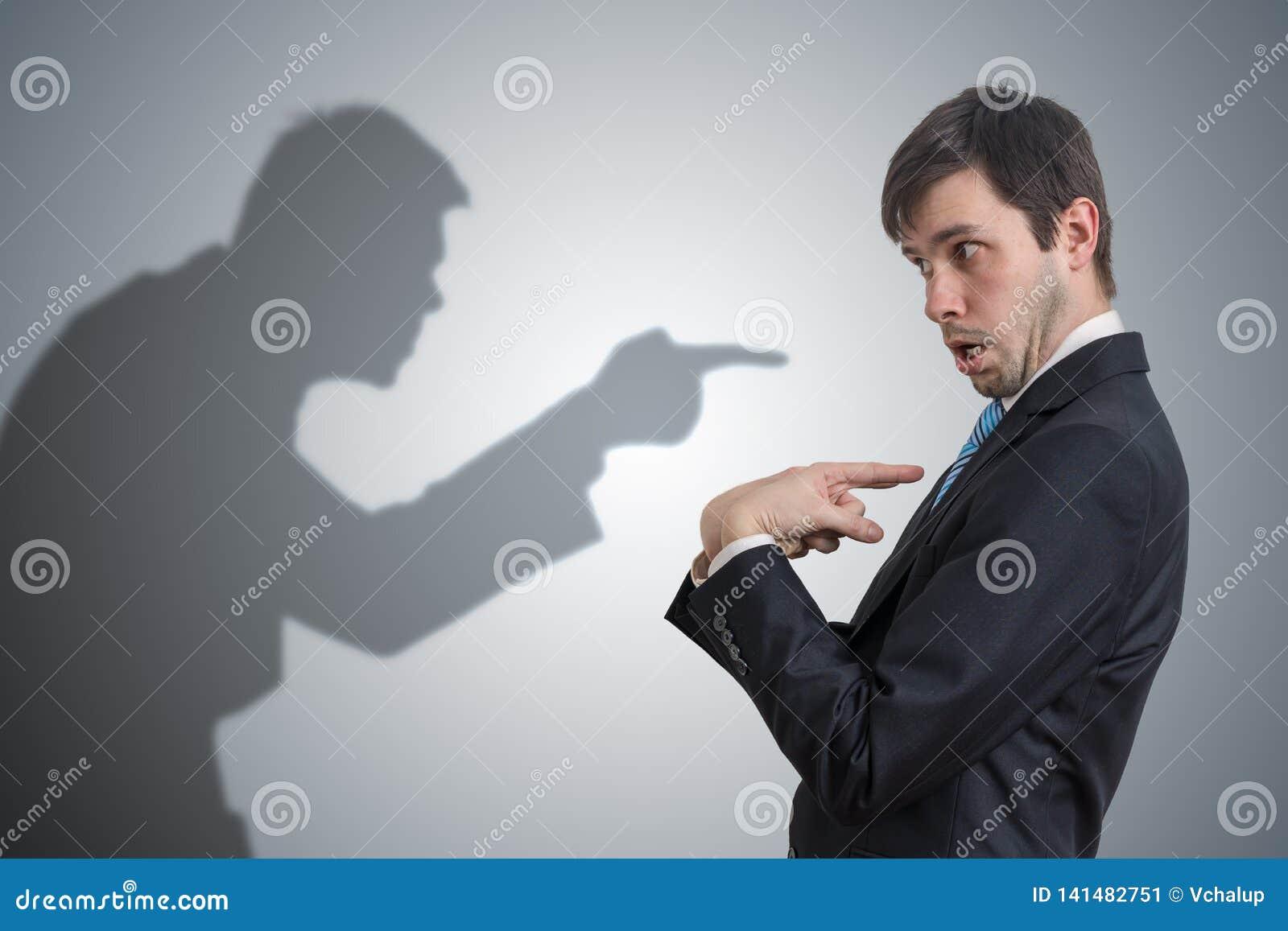 A sombra do homem é apontando e de acusação o homem de negócios Conceito da consciência