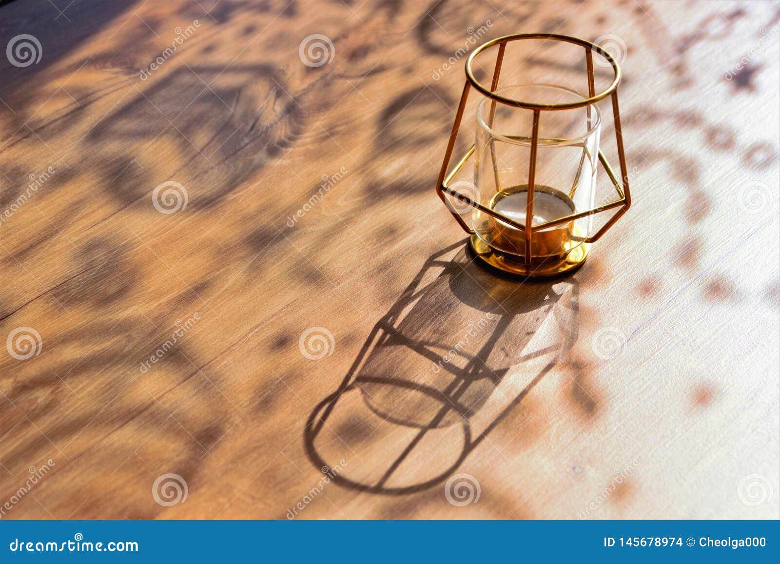 Sombras encaracolados em uma tabela de madeira em um dia ensolarado, castiçal do desenhista, close-up, foco seletivo, espaço da c