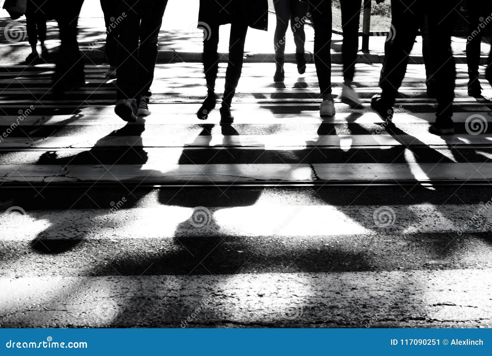 Sombras y siluetas borrosas de la gente en cruce