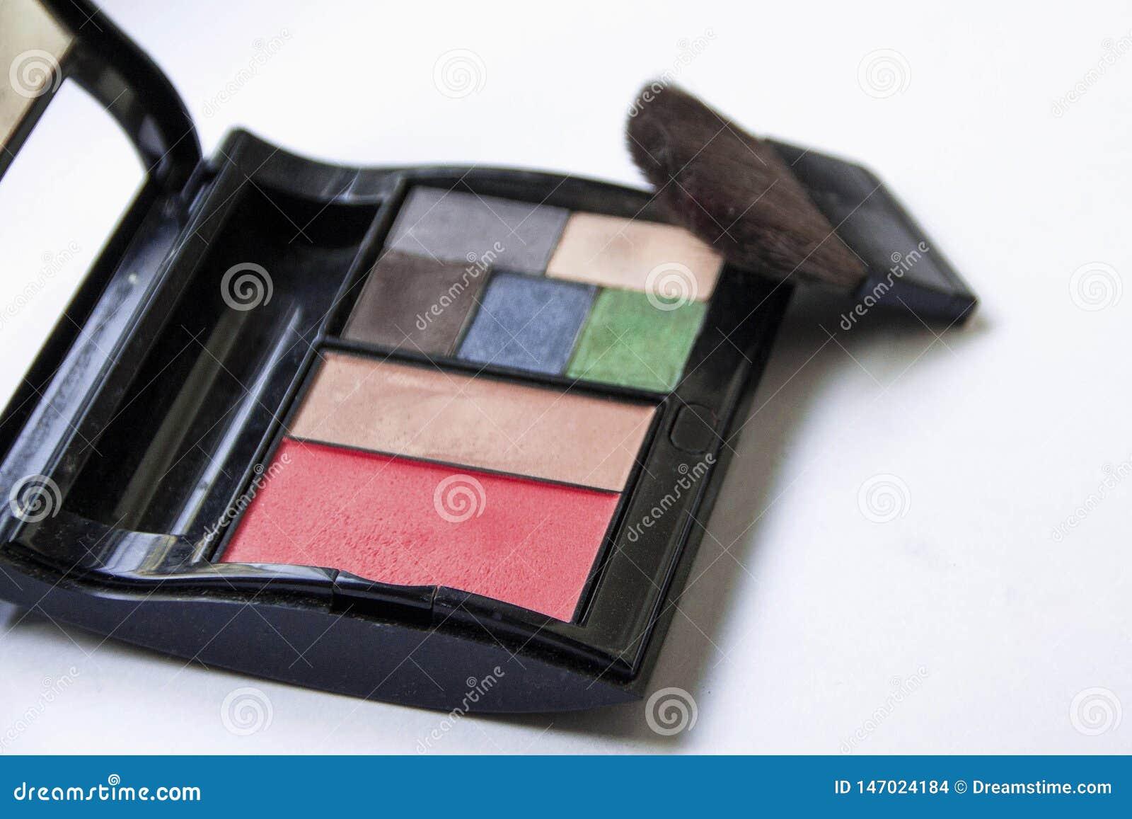 Sombreadores de ojos y cepillo y cosm?ticos del maquillaje, en un fondo blanco aislado,