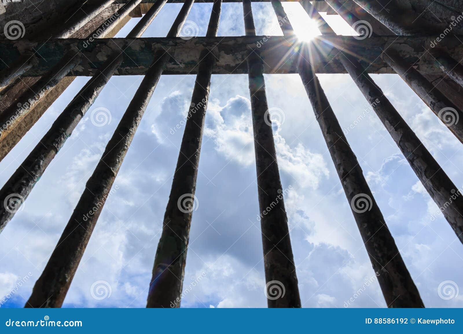 Sombreie o brilho através das barras da prisão velha