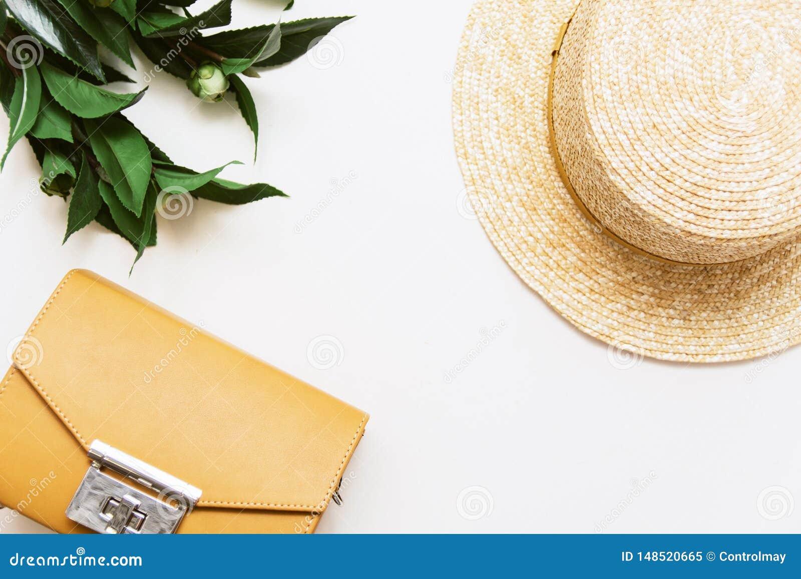 Sombrero amarillo del bolso, de la planta y de paja en un fondo beige
