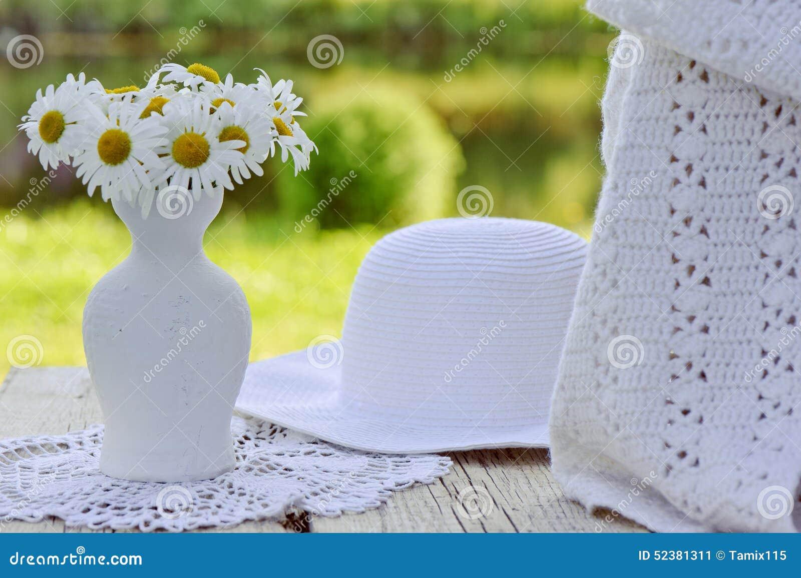 Sombrero, bufanda y ramo blancos de manzanilla en florero