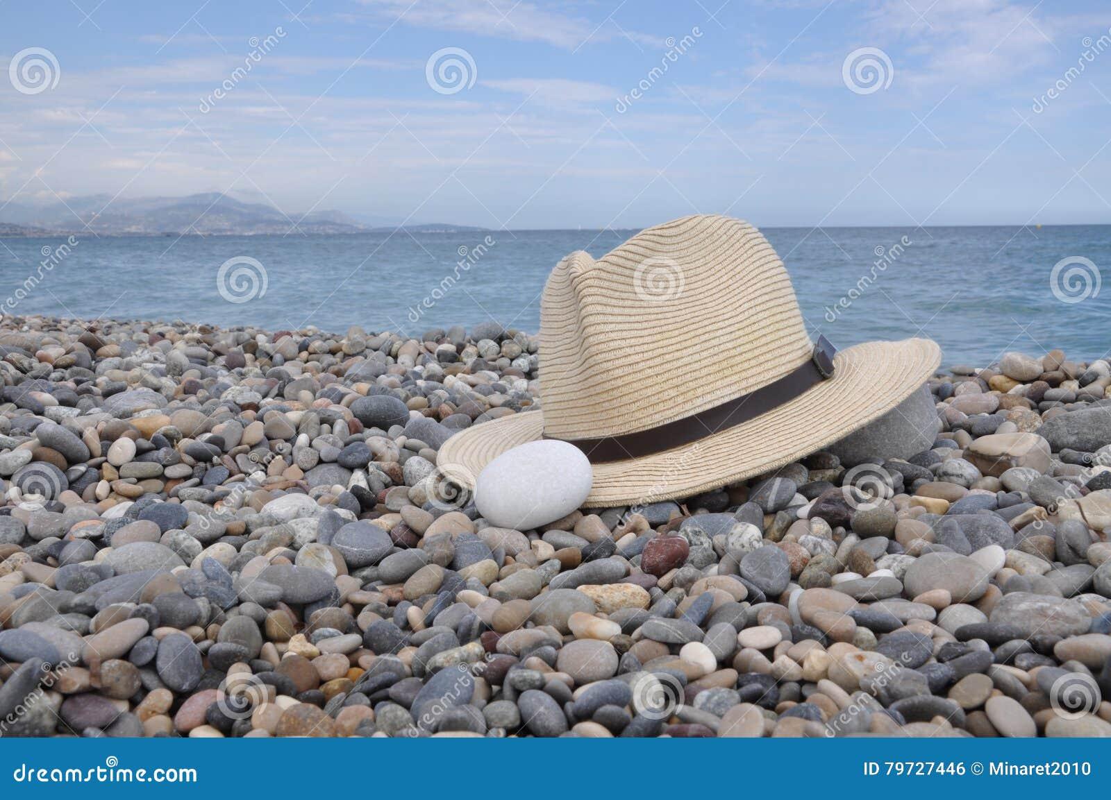 Sombrero en la playa de piedra en la costa
