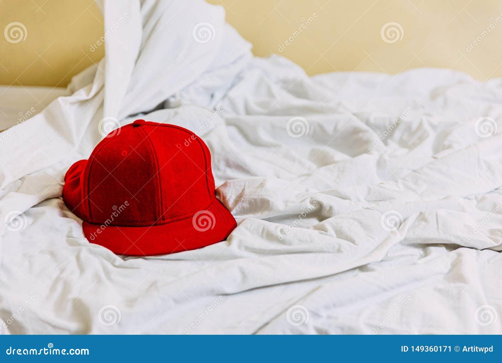 Sombrero rojo en el lado izquierdo sobre la manta blanca en la cama con el fondo amarillo