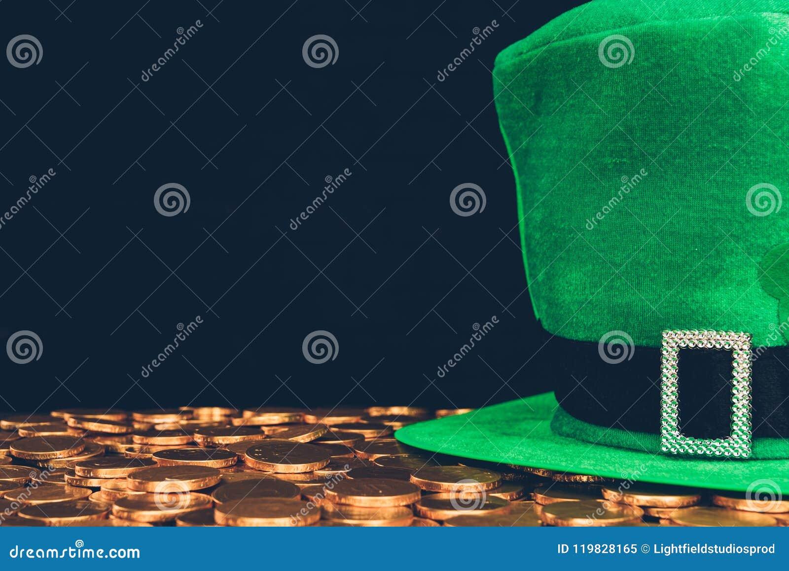 Sombrero verde en las monedas de oro aisladas en el negro, concepto del día de los patricks del st